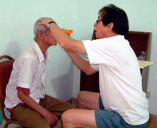 Dr. Guillermo de Venecia examines a patient's eye at the Free Rural Eye Clinic in the Philippines. The Eye Clinic was a labor of love for De. de Venecia and many residents trained there. The gift to the Department will continue his work.