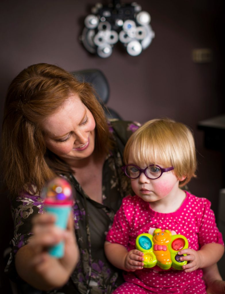 Woman is Holding a Toy in Front of a Child Wearing Glasses