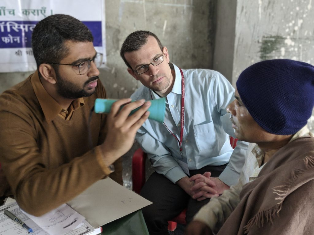 Resident, Dr. R. Chris Bowen observers eye exam at outreach clinic in New Delhi, India during rotation February 1-15, 2019.